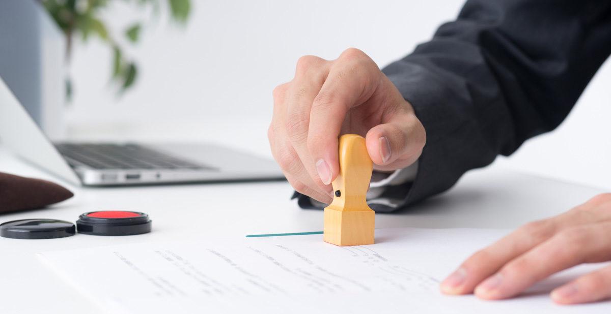 書類に法人印鑑の角印を押すサラリーマン